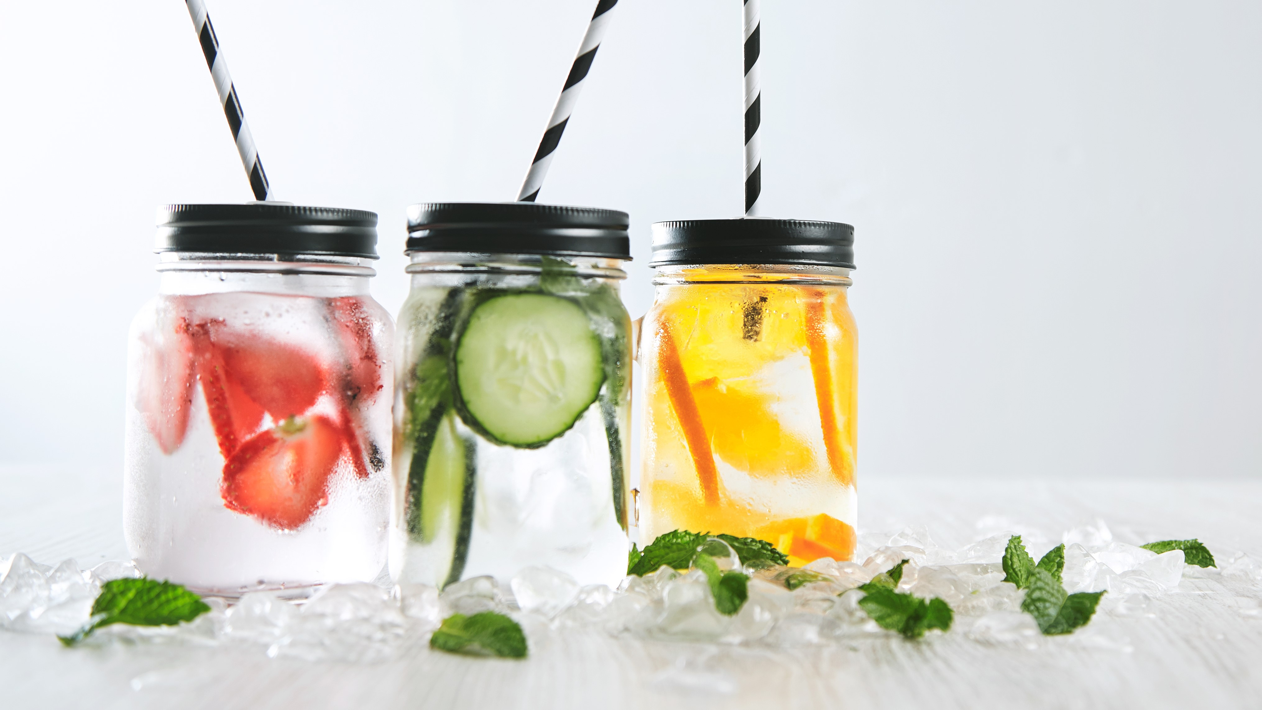 Three cold refreshment beverages from strawberry,cucumber,lime,mint,ice and sparkling water in rustic jars with drinking straws inside,isolated,focus on orange lemonade